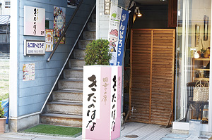 ▲ピンクの看板が目印。階段を登った先が入口です。